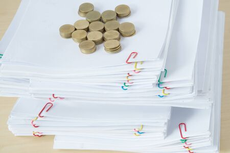 Pile of overload paperwork and reports with colorful paper clip have blur pile of gold coins place on wooden table.