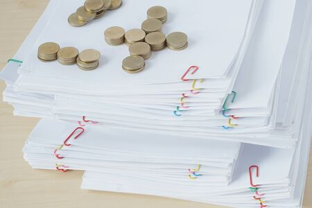 Pile of gold coins on pile of overload paperwork and reports with colorful paper clip place on wooden table.