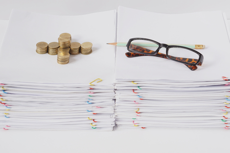 Spectacles and pencil with pile of gold coins place on pile of overload paper and reports with colorful paper clip on white table. Stockfoto