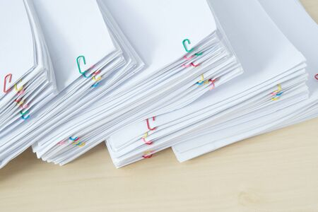 Pile of workload paper and reports with colorful paper clip place on wooden table.