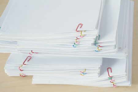 Pile of workload paperwork and reports with colorful paper clip place on wooden table.
