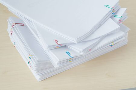 Pile of overload paperwork and reports with colorful paper clip place on wooden table.