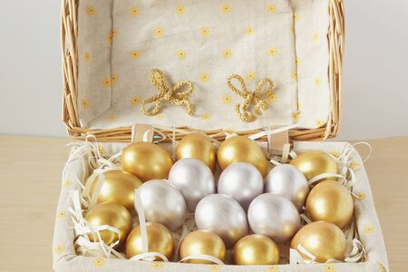 Gold and silver eggs laid in a basket on a wooden table.