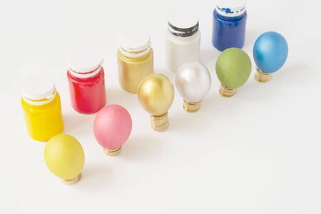 Colorful eggs put on pile of gold coins with bottle on a white background.