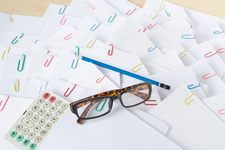 Calculator with spectacles put on stack of overload paper and reports with blue pencil place on wood table.