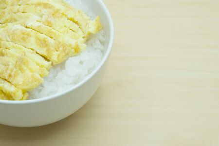 Soft boiled rice and omelet in  bowl placed on a wood table.