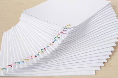 Colorful paperclip with pile of overload white paperwork and reports arranged on wood table. Stockfoto