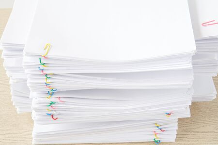 Colorful paperclip with pile of overload white paperwork and reports on wood table.