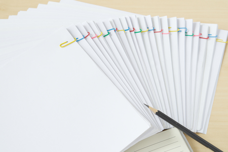 Pencil with notebook and colorful paperclip with pile of overload white paperwork and reports arranged on wood table Stockfoto