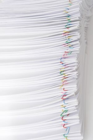 Colorful paperclip with pile of overload white paperwork and report on wood table.