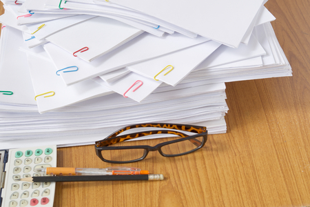 Glasses and paperwork with colorful paperclip and calculator with pen and pencil placed on wood table. Stockfoto