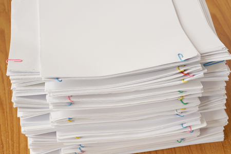 Colorful paper clip with pile of overload document and reports place on brown wooden table.