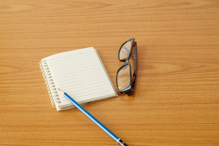 Notebook and glasses have pencil place on brown wooden floor.