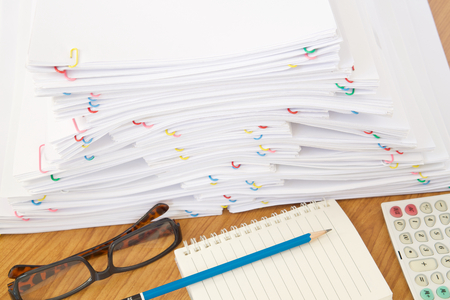 Stack of overload paper and reports have blue pencil on notebook with spectacles and calculator place on brown wood table.