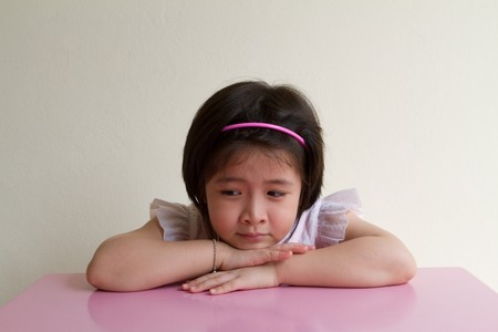 little asian girl sleep at pink table photo