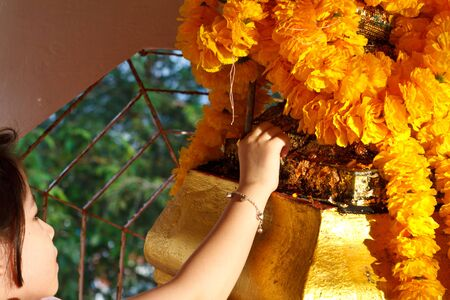 Little Girl Respect Buddha in Thai Temple photo