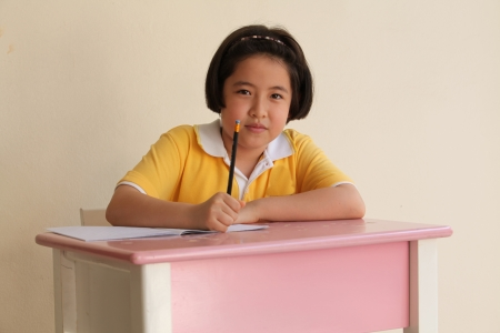 Young attractive female Asian student sitting at her desk and writing photo