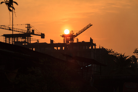 Construction crane and skyscraper at sunset photo