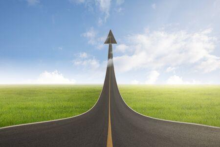 Una strada che si trasforma in una freccia che sale verso l'alto con successo, a simboleggiare la direzione verso il successo