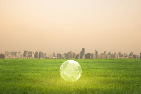 The  globe with the background of many large building. Global warming and pollution theme . Conceptual image symbolizing global warming leading to destroying the natural ecosystems of our planet.