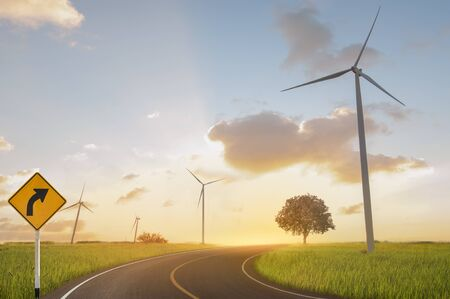 Green energy concept. Road in green field with wind turbines and sunset backgrounds