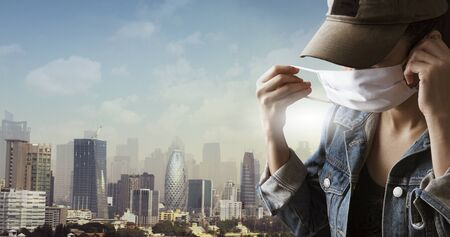 A tourist wearing a mask isolated on city background. Promoting people use face mask to protect themselves from virus infection in Corona virus crisis 2020 Reklamní fotografie