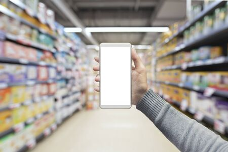 Female hand holding mobile smart phone on Supermarket blur background, business concept 版權商用圖片