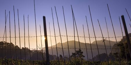 image of foggy mountain and barbed wire wall in sunny day.
