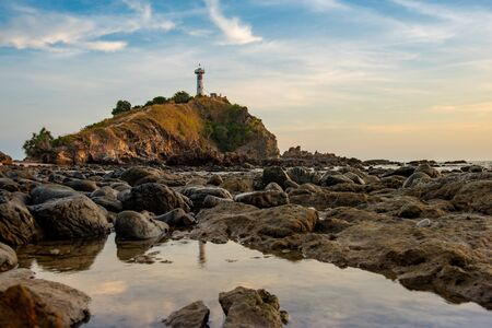 Light house at Lanta Krabi with water reflection and sky during sunset. Travel destination and nature environment concept.