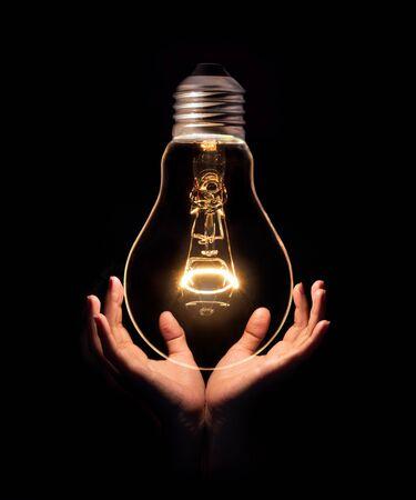 Lightbulb on hand isolate on black background.Energy or idea concept