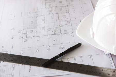 Close-up of blueprints with sketches of projects, pen, ruler and white helmet.