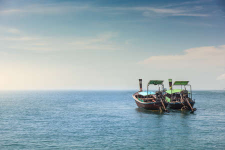 Two long tail boat in sea water is waiting for tourists passengers go back to local islands in the evening.