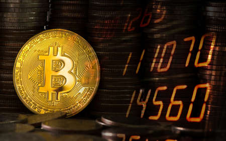 Close-up bitcoin on the background of coins of baht. Stocks Exchange Market Graph Concept.