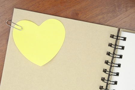 Yellow notepaper in heart shape cliped on blank notebook photo