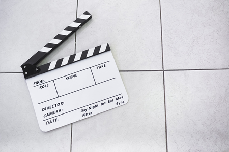 Movie clapperboard on the tile floor.