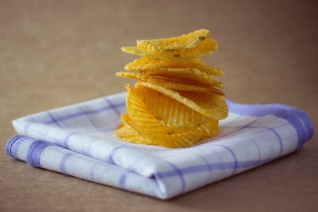 unhealthful: Potato chips on brown background