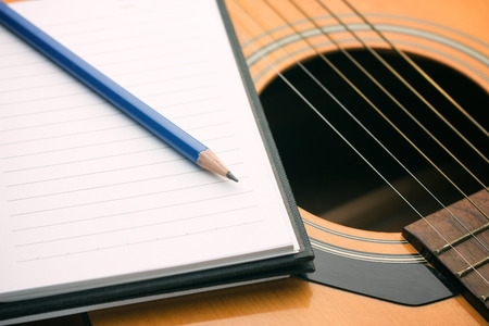 Notebook and pencil on guitar,Writing music photo