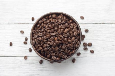 cafe colombiano: Granos de café en un tazón de madera en la mesa de madera