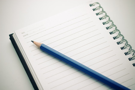 Notebook and pencil on white background photo