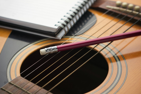 Notebook and pencil on guitar, Writing music Stock Photo
