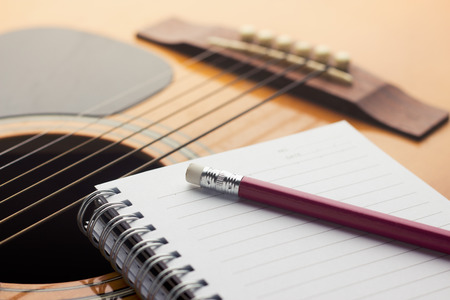 Notebook and pencil on guitar, Writing music photo