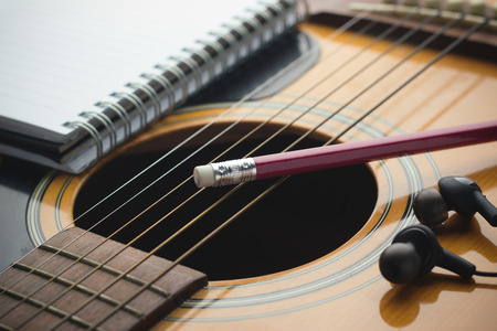 Notebook and pencil on guitar, Writing music Stok Fotoğraf