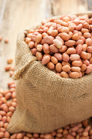 earthnuts: Peanuts in a small Sack on wooden background Stock Photo