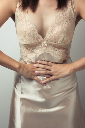 sleepwear: Young casual girl woman is having stomach ache