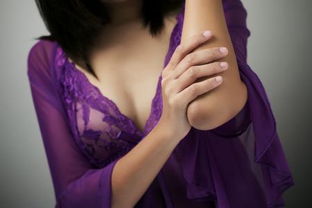 codo: Mujer adulta con dolor en el codo