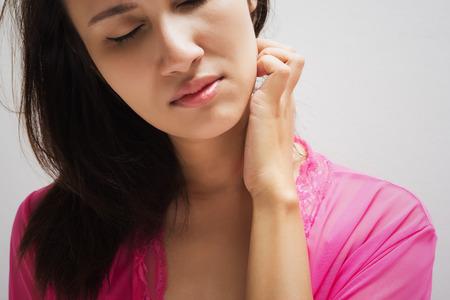 Young beautiful woman scraching her neck