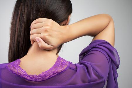 cabeza de mujer: Joven mujer que tiene dolor en la espalda y el cuello, dolor en la espalda Foto de archivo