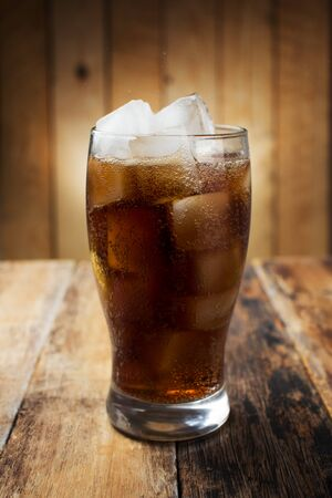 co action: A glass of cola with ice cubes