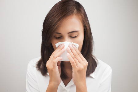 sick leave: Business woman sneezing while working in office, Businesswoman having flu