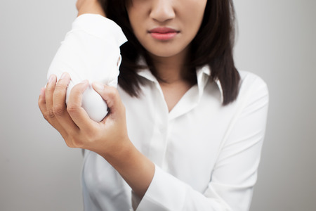 elbow pain: Business woman suffering from elbow pain